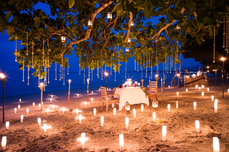 Set dinner table for two on the beach at night, surrounded by lit lanterns on the sand and lit lanterns hanging from the trees above the table.
