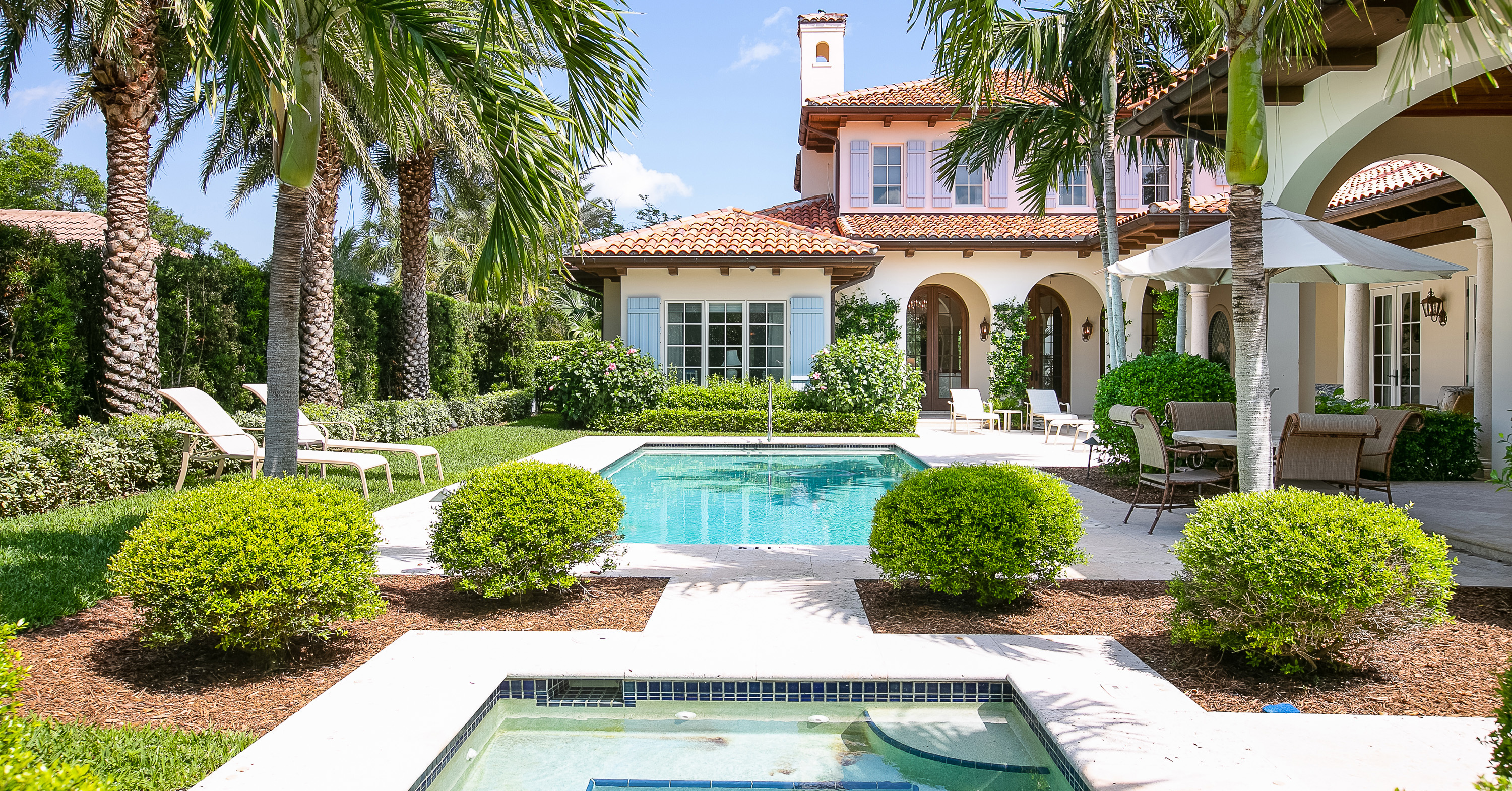 Exterior of backyard of large luxury mediterranean home with pool, hot tub and large palm trees