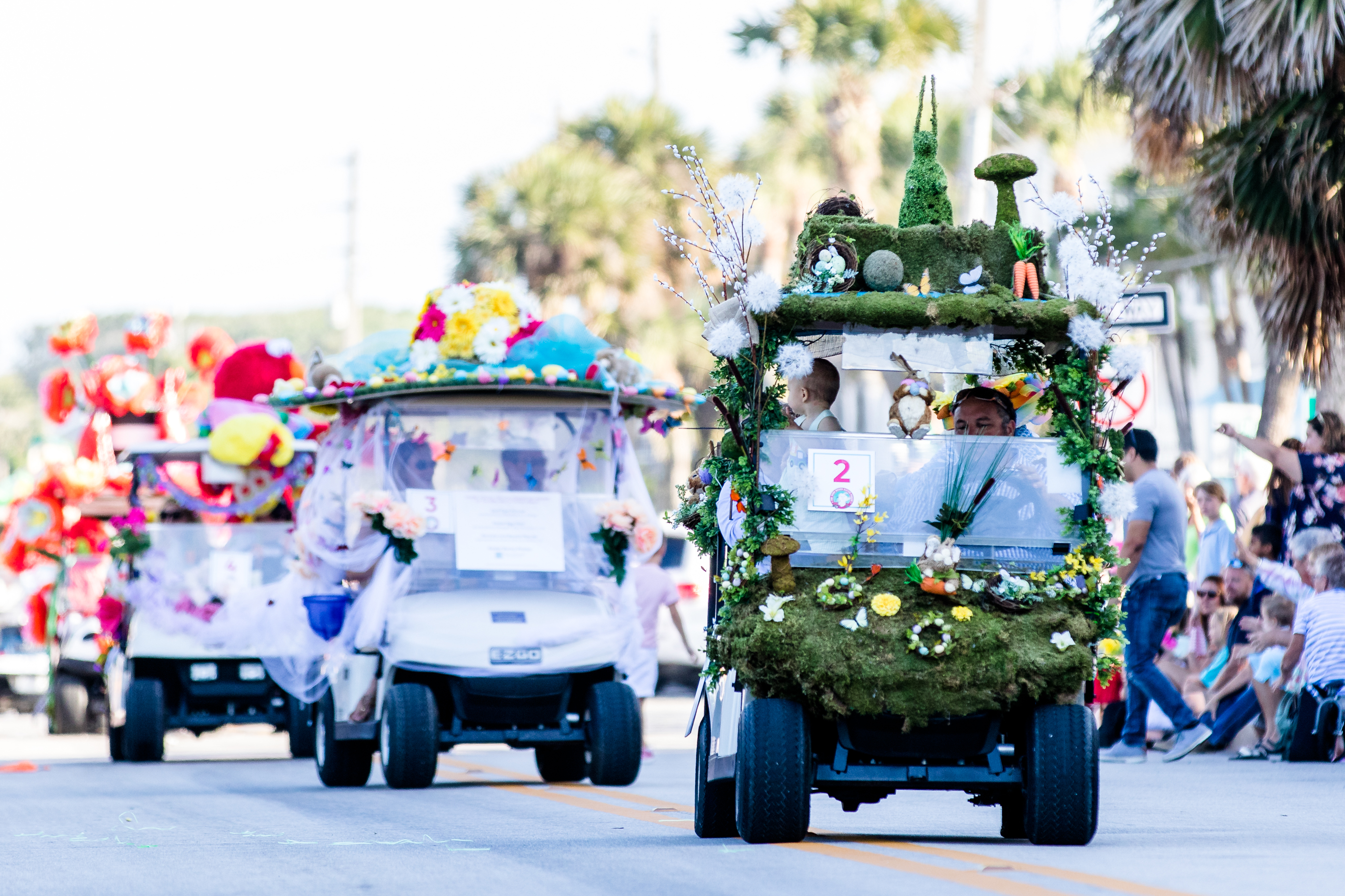 Golf carts on parade covered in flowers and greenery